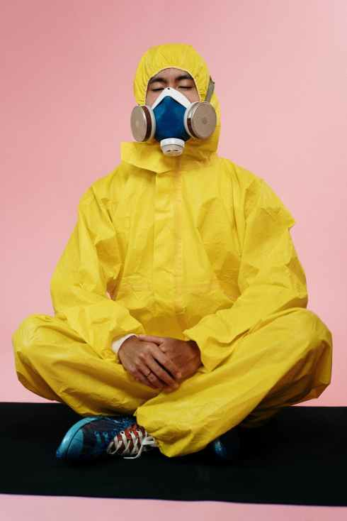 person in yellow protective suit meditating